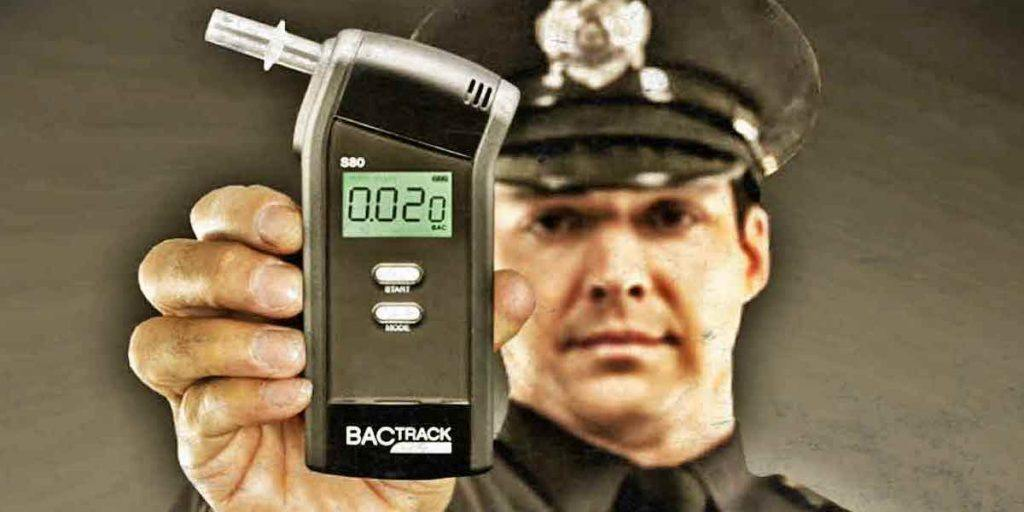 Police officer holding breathalyzer device